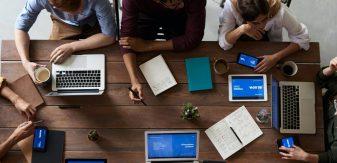 Personnes travaillant atour d'une table avec des ordinateurs